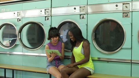 Two Young Women wait for the laundry whilst sharing a Digital Tablet