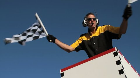 Slow motion version of race official waving a checkered flag at an auto race. View is from the track looking up.
