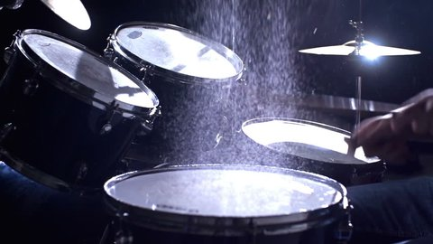 Close up of drums perfused with water for special effect hit by unrecognizable guy in slow motion
