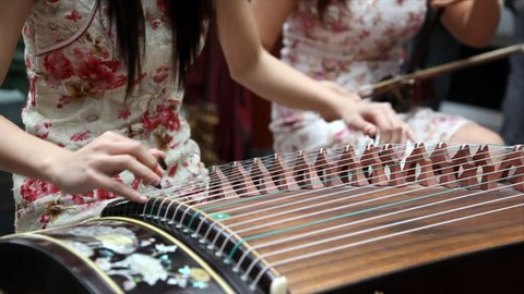Chinese traditional musician playing Chinese guzheng. Guzheng, also called zheng or Chinese plucked zither,is a plucked half-tube zither with movable bridges and strings