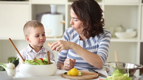 Mother and son making salad and having fun