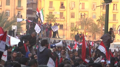 Large crowd of demonstrators inside Tahrir Square, Cairo on 1st anniversary of Egyptian Revolution.  Men wave Egyptian flags, revolutionary Syrian flags, Arabic banners.   25 Jan 2012