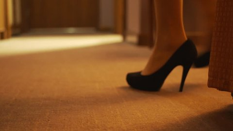 Beautiful young girl walks into frame in high heels in her hotel room before taking them off and walking to the bathroom. Shot focuses on her feet and stilettos. Warm lighting.