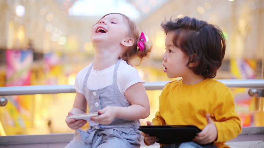 Little pretty girl with mobile phone and boy with tablet pc sit on floor in mall