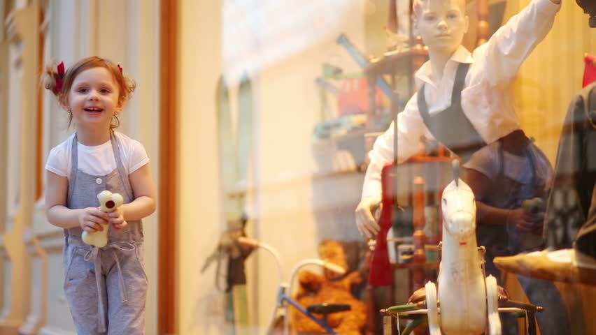 Little cute girl holds toy bone and looks at shop window in mall