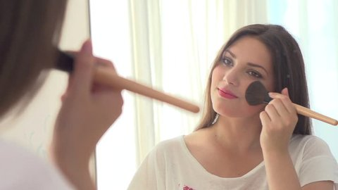 Beauty woman applying makeup. Beautiful girl looking in the mirror and applying cosmetic with a big brush. Girl gets blush on the cheekbones. Powder, rouge. Slow motion video footage 1080 full hd
