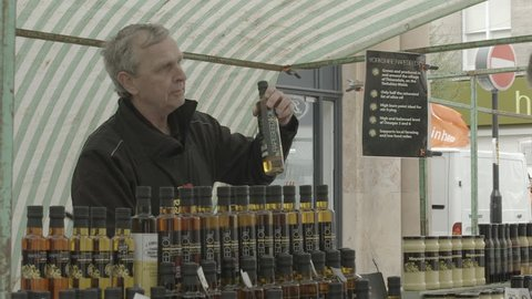 England - CIRCA 2014: Market stall man chatting and selling to customers enthusiastically about his rapeseed oil bottle product. Filmed at Harrogate Farmers Market, UK.