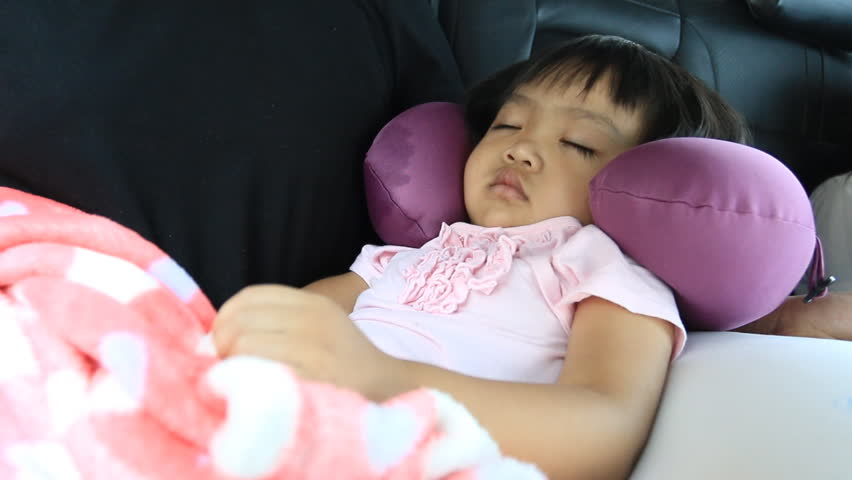 Asian child sleeping in a car