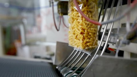 Raw rotini scroodle fusilli envelopes in a pasta factory.