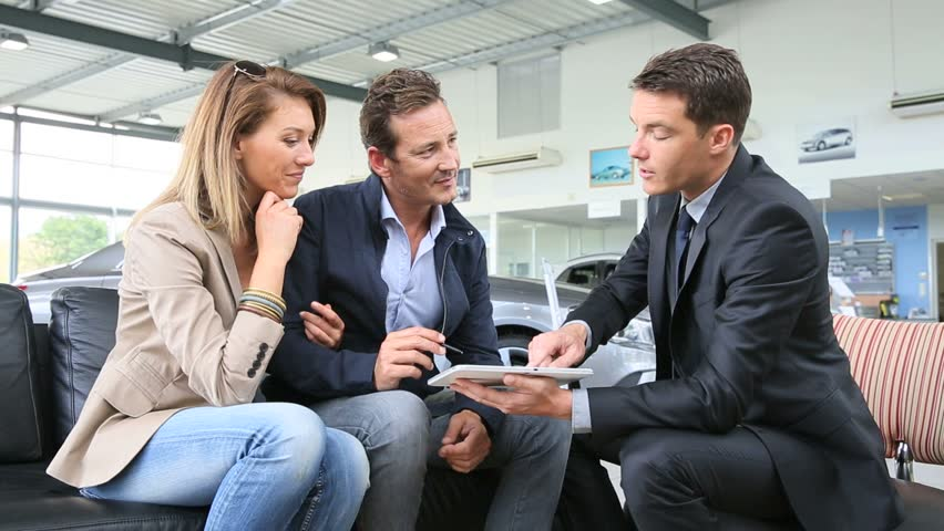 Couple with car dealer signing purchase contract on tablet | Shutterstock HD Video #6623168