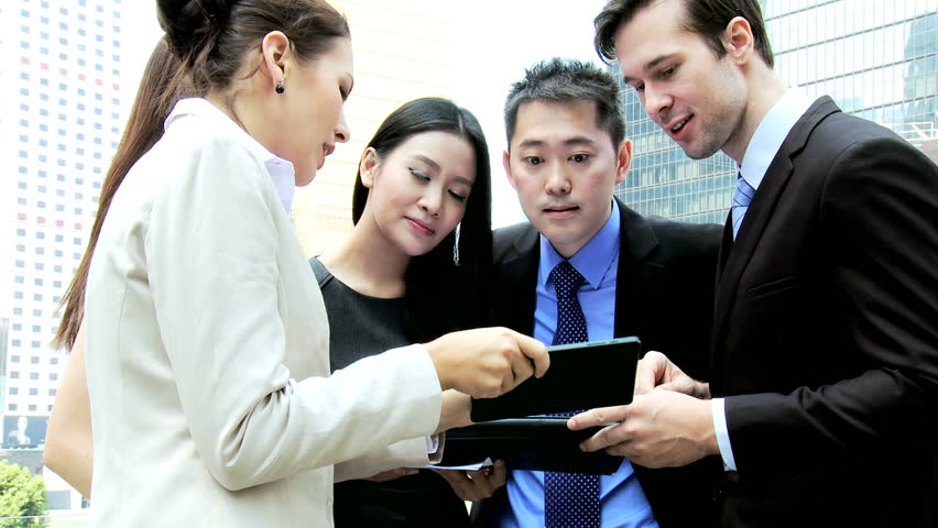 Male female Caucasian Asian Chinese financial team smart business clothes city downtown hot spot outdoors wireless mini tablet technology | Shutterstock HD Video #6646697