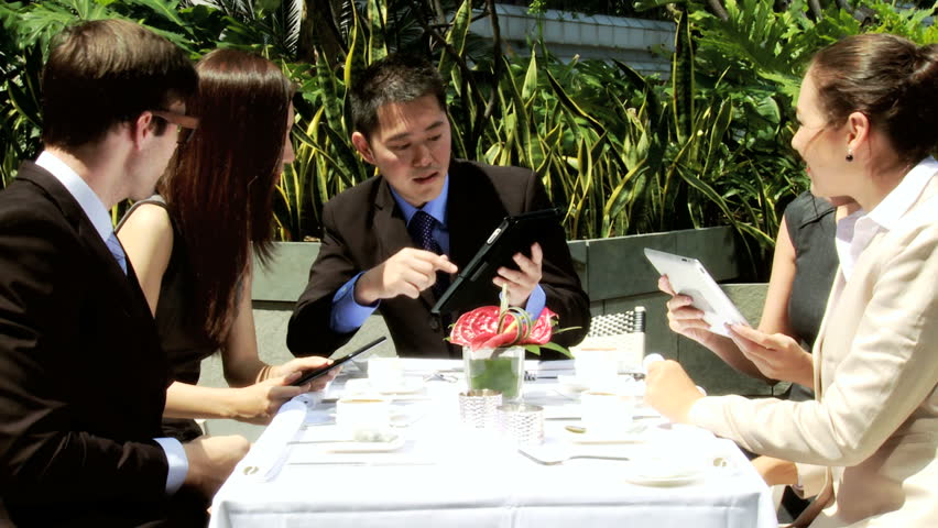 Group male female Asian Chinese Caucasian business people wireless tablets meeting drinking coffee city rooftop restaurant | Shutterstock HD Video #6646931
