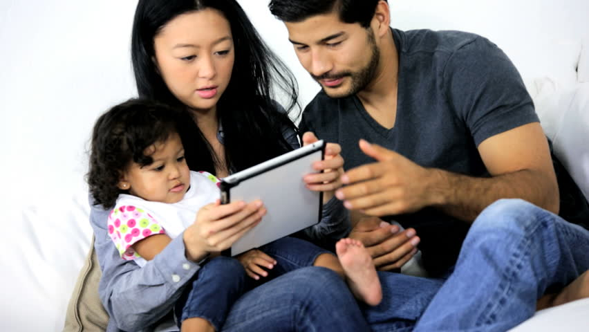 Happy young Asian Chinese couple pre school daughter playing online games together home modern touch screen technology wireless tablet | Shutterstock HD Video #6657671