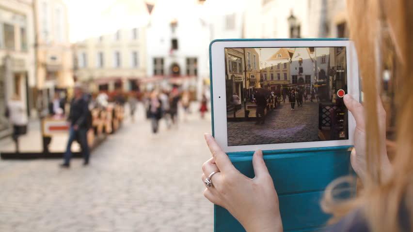 Close-up shot of womans hands using touchpad to make video of ancient street in Tallin, Estonia. Then she playing video