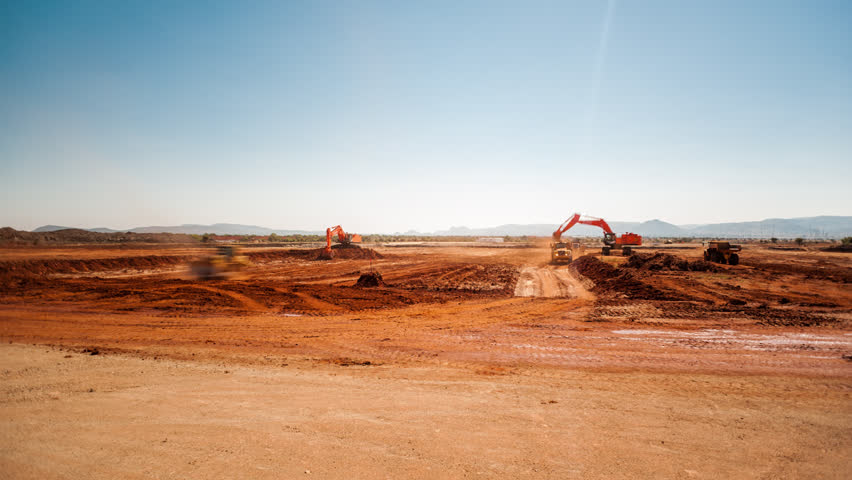 Static pan timelapse of a construction site on a mine while earthworks is in progress with heavy load machinery, trucks and tippers close to action.