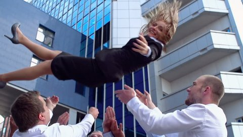 Business team celebrating success outdoors tossing leader in the air
