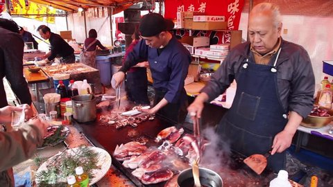 TOKYO, JAPAN - CIRCA APRIL 2014: People, food stall, cherry blossom, Ueno Park. Crowd, tourists and small family business, family-run activity selling seafood circa April 2014 in Tokyo, Japan, Asia
