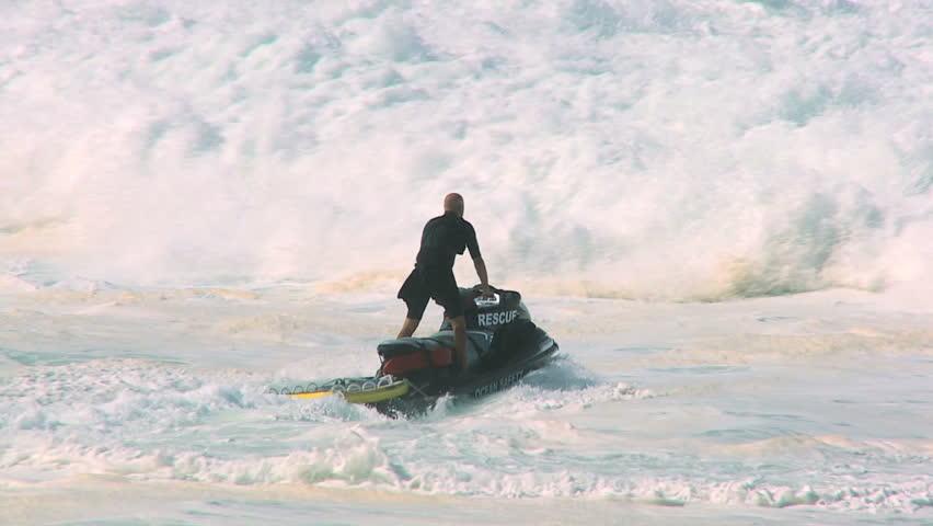 Dramatic shot of lifeguard launching rescue jet-ski into crashing giant waves 60 FPS