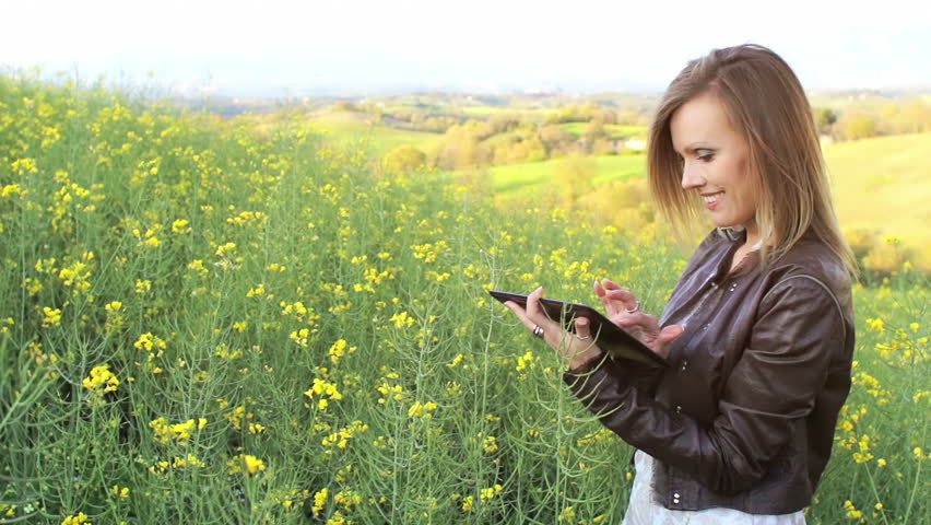 Businesswoman with electronic tablet standing in yellow rape field