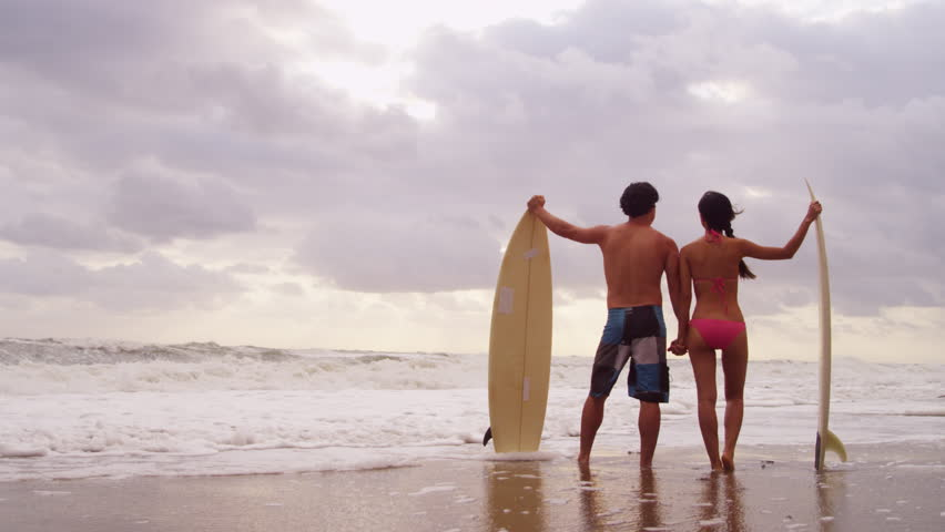 Young Asian Chinese male female surfers wearing swimwear standing beach sunset watching ocean waves carrying surfboard tourism promotion shot on RED EPIC   Shutterstock HD Video #6786571