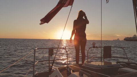 A young woman dives into the water from a sailing boat at sunset / Ibiza, Spain