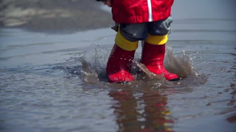Close up of unrecognizable kid feet in rubber boots bouncing in pool