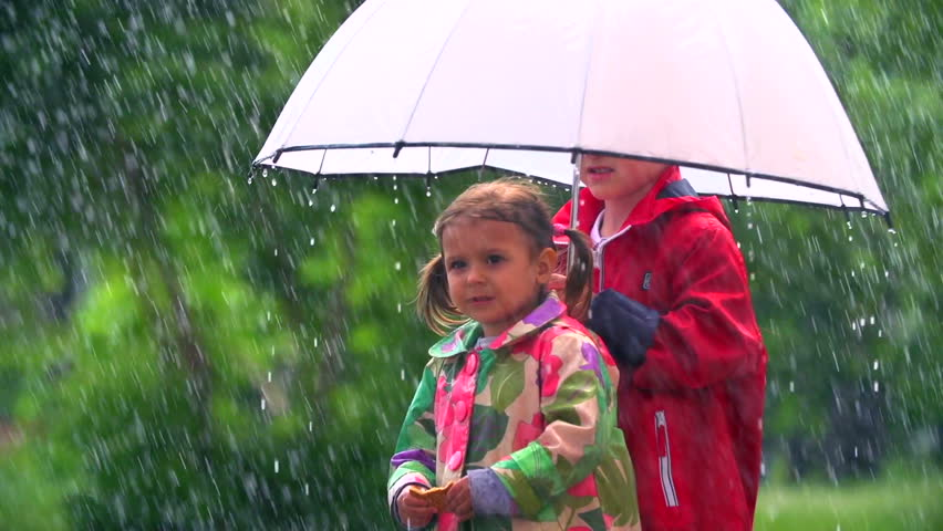 Kids standing with umbrella under pouring rain
