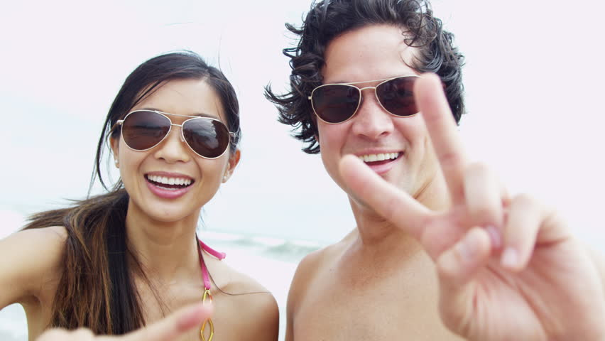 Laughing young Asian Chinese couple head shoulders having fun swimwear  beach smiling to camera hand signs filming social media video self portrait  full ...
