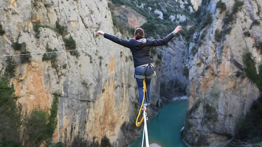 France, 2013. A woman tightrope walking over high canyon lost her balance and hangs from the rope.