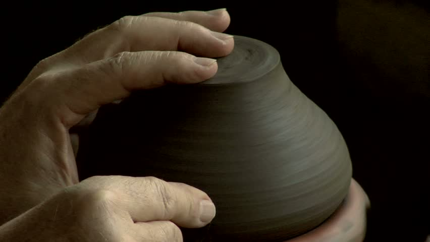Close up of a man's hands making a clay pot