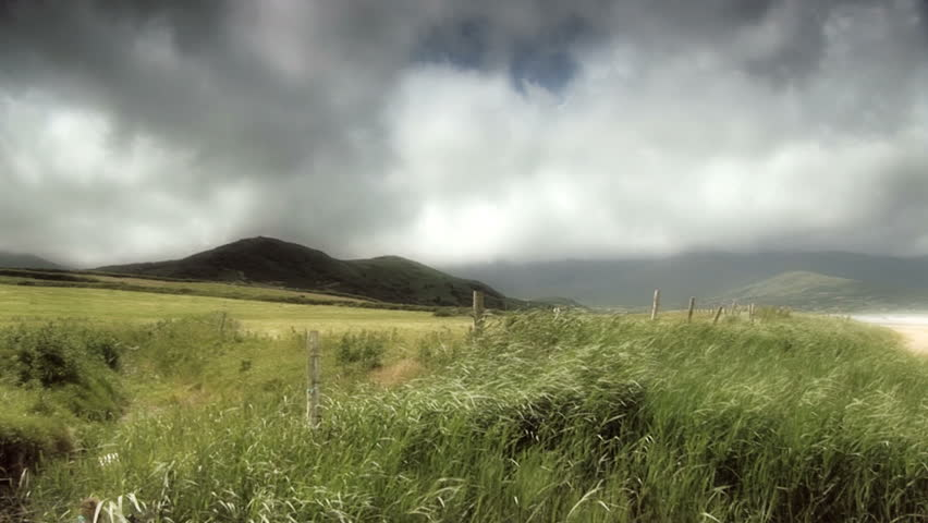 Irish valley with grasses blowing in the wind.  It is a cloudy day with lots of sun.