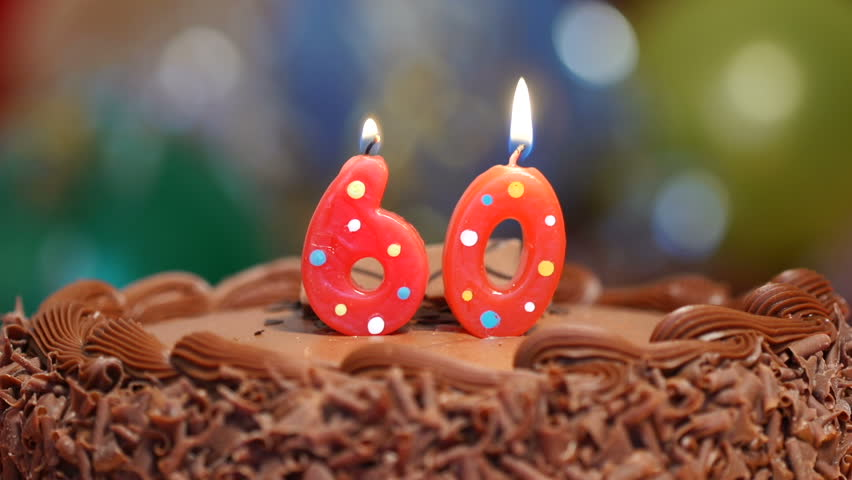 Candles on a cake are blown out for a 60th birthday - sixty years old