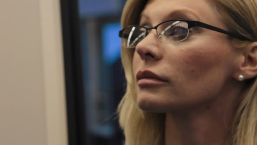 Female commuter uses digital tablet on train, seen reflected in her glasses   Shutterstock HD Video #6857971