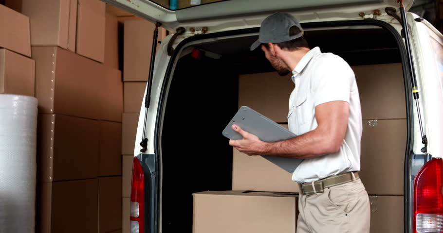 Delivery driver checking his list in a large warehouse | Shutterstock HD Video #6858061