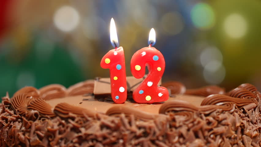 Candles On A Cake Are Blown Out For 12th Birthday