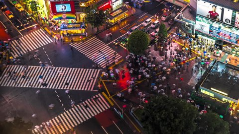 TOKYO, JAPAN - MAY 16, 2013: Time lapse video of people with umbrellas cross the famous diagonal intersection in Shibuya, Tokyo, Japan.