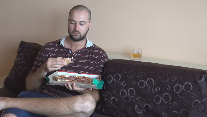 Handsome Boy At Home Relaxing On Sofa Eating Pizza And Drinking Beer Great Meal