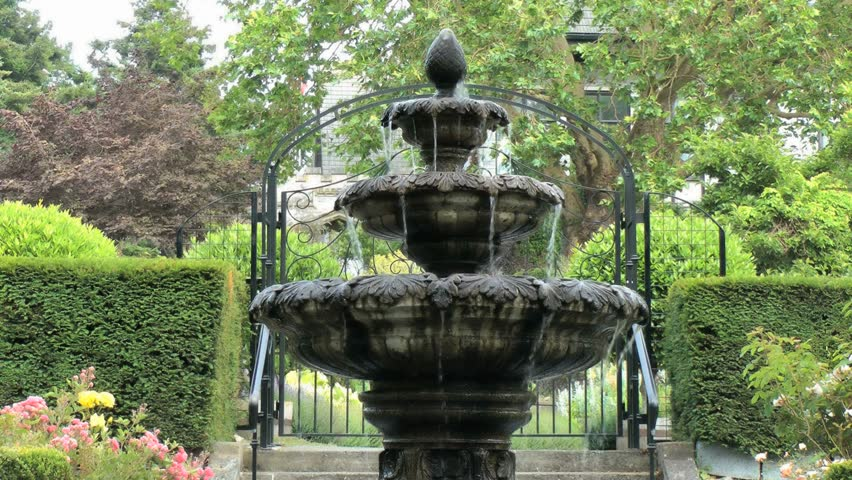 Water Fountain In Front Of An Iron Gate A Formal English Garden
