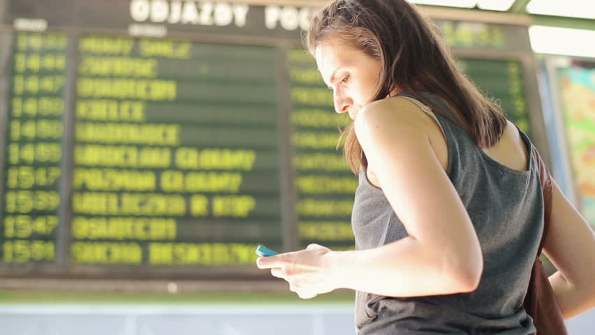 Woman looking at timetable departure board at train station