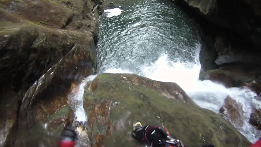 A canyoneer jumps into the water, goes under then comes back up, POV shot