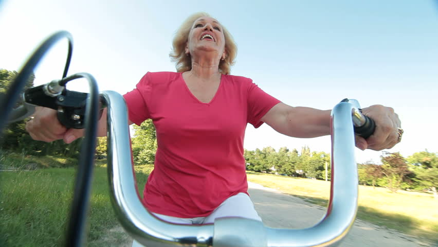 Happy senior woman riding bicycle waves his hand smiling | Shutterstock HD Video #6940705