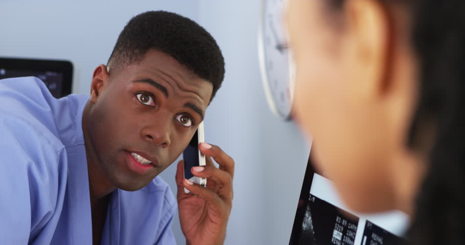 Close up of African American doctor talking to female colleague while using smartphone | Shutterstock HD Video #6999808