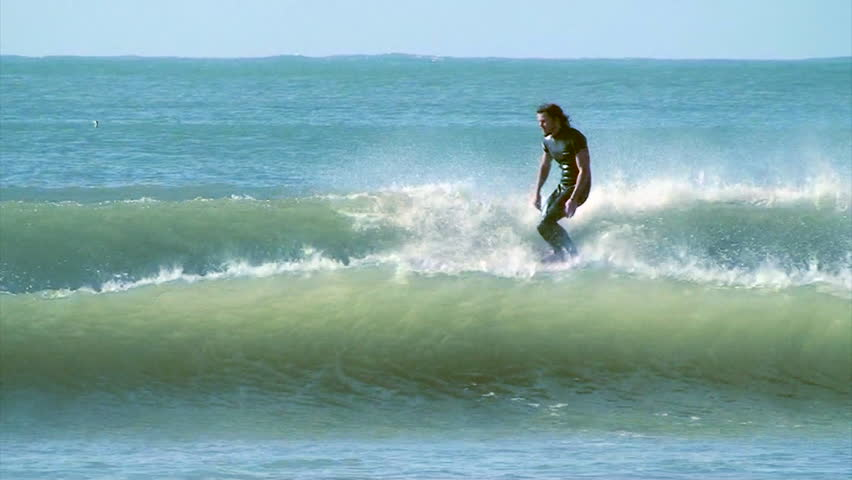 A surfer nose riding on a longboard whilst hanging ten | Shutterstock HD Video #7032931