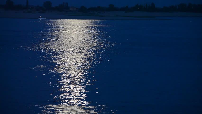 Beautiful lunar path reflection on a dark blue water background | Shutterstock HD Video #7050811