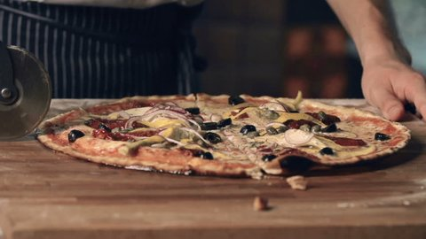 Close up of pizza professionally and carefully sliced by unrecognizable cook