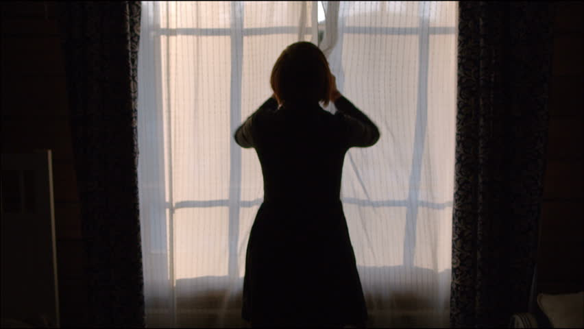 Young woman opens the window indoors