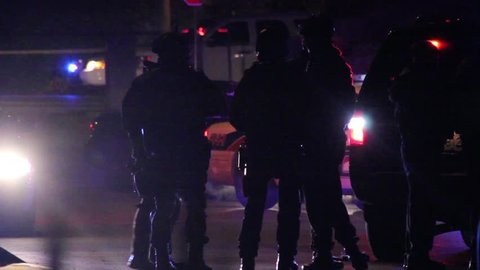 Vancouver, Canada - April 2013 - Silhouette of SWAT officers with riffles standing by police truck