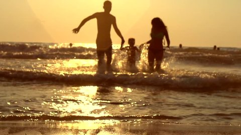 Happy family with a child on vacation at the beach. Smiling Parents with a Little daughter Have a Fun running out of the Sea Splashing and Holds Child By Arms. Over sunset. Slowmotion 240fps 1920x1080
