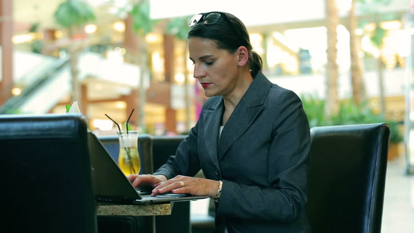 Businesswoman working on laptop and answering phone in the restaurant