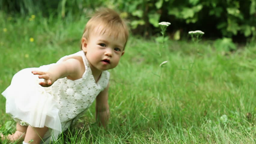 A happy smiling baby girl in a dress crawling on a green grass, slow motion, steadicam shot #7190461